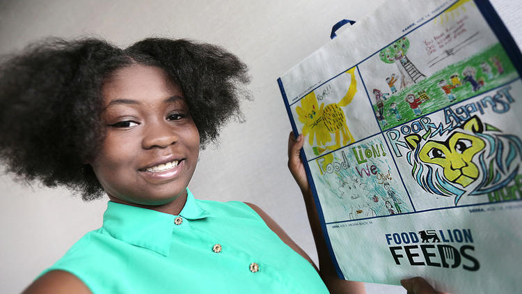 Sierra Harris, who attends Woodside High School, was one of the winners in Food Lion's design a reusable tote contest. Her design is the yellow lion bottom right. She said she heard about the contest from her aunt who manages a Food Lion. (Judith Lowery / Daily Press)